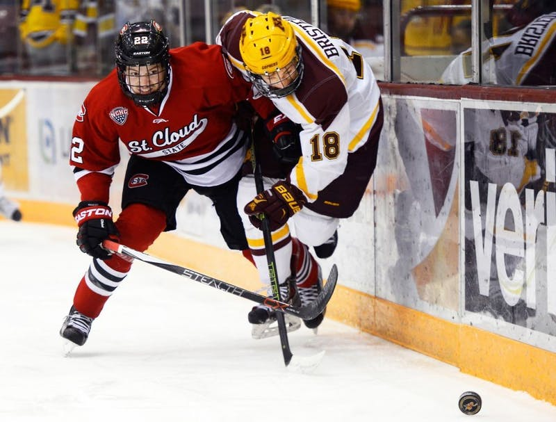 Gophers forward Leon Bristedt struggles to hold the puck against St. Cloud State defender Jimmy Schuldt at Mariucci Arena on Friday, Nov. 27, 2015.