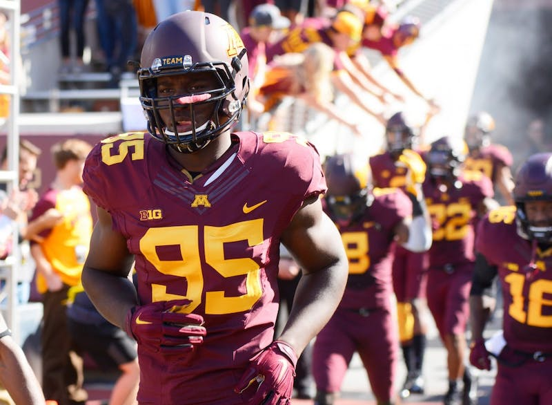 Defensive Lineman Hendrick Ekpe runs through the tunnel and on to the field at TCF Bank Stadium on Sept. 19. The Gophers defeated Kent State University.