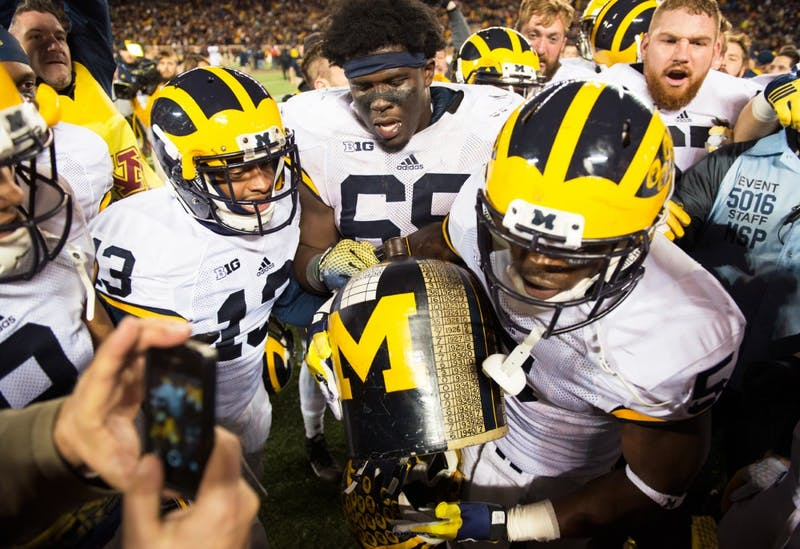 The University of Michigan football team celebrates after claiming the Little Brown Jug trophy at TCF Bank Stadium on Saturday, where the Wolverines defeated the Gophers 29-26.