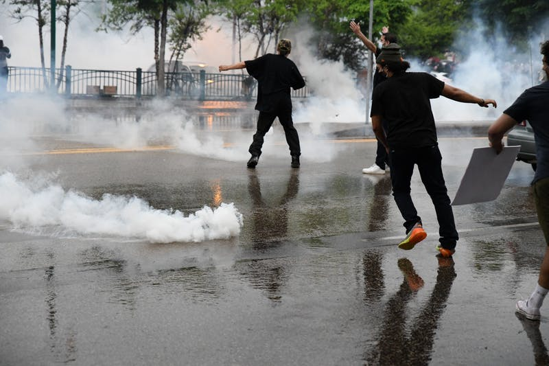 Protesters dodge tear gas cannisters outside of the Minneapolis 3rd Police Precinct on Tuesday, May 26.