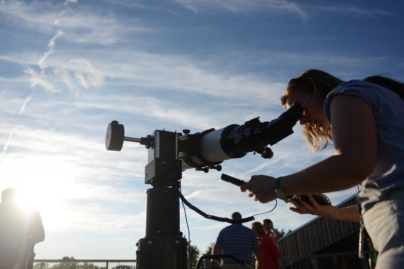 Sarah Komperud dials in a telescope from a cell phone to connect with the setting sun, with the goal of viewing sunspots.