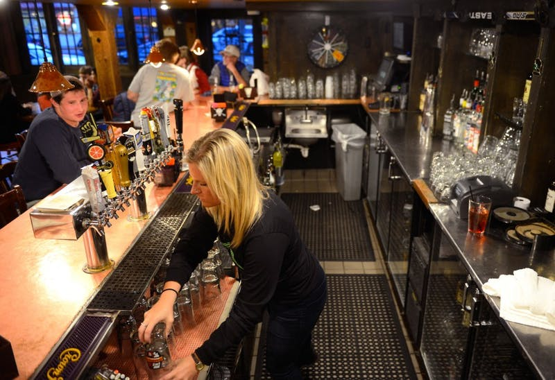 Bartender Libby Kvasnicka washes glasses at Blarney Pub & Grill on Saturday. This fall, The Department of Public Safety and State Gambling Control Board will begin running checks for compliance to liquor and gambling laws, tightening down on college bars to better enforce existing laws.