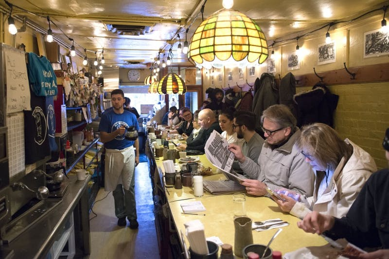 """Employee Will Harris carries a pot of coffee while Dean Schieve reads the paper and wife Mary scrolls through her phone in Al's Breakfast on Monday, Jan. 25, 2017. Dean said he's been coming to Al's since he was a student in 1987. """"I like the ambience and the people,"""" he said. """"It's a pretty cool place to come and read the paper."""""""