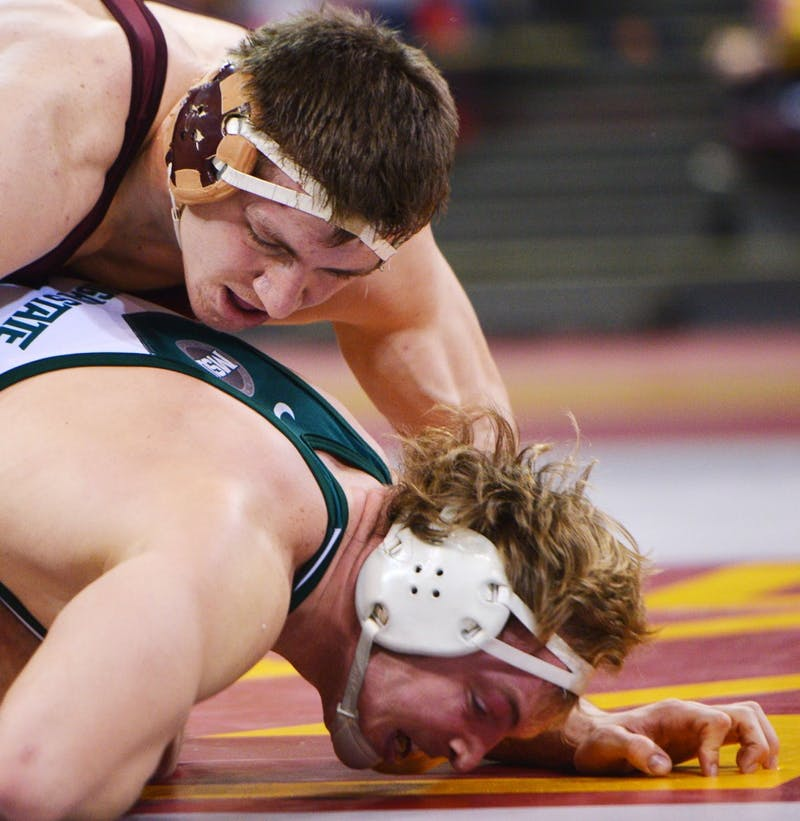 Minnesota's Tony Nelson holds down Michigan State's Michael McClure on Sunday, Feb. 3, 2013, at the Sports Pavilion.