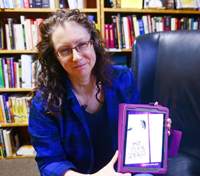 """Rachel Gold poses with the cover art of her new book at the Book House in Dinkytown on Sunday. Gold will be reading a section from her book, """"My Year Zero"""" at the Queer Voices event on Tuesday."""