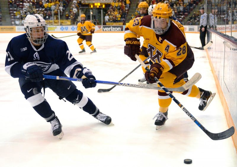 Gophers defense Jake Bischoff fights to maintain control of the puck while playing against Penn State in Mariucci Arena on Saturday, Feb. 6, 2016.