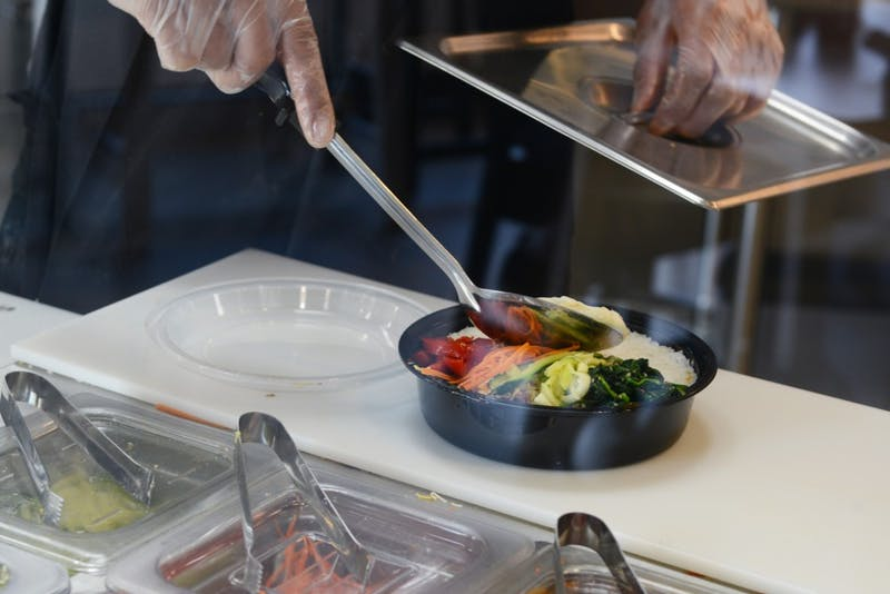 Ed Eubanks prepares an asian burrito bowl at Burrigato, a new restaurant in Dinkytown, on May 3, 2017.  The restaurant has been serving asian style burritos and rice bowls since it opened on April 20.