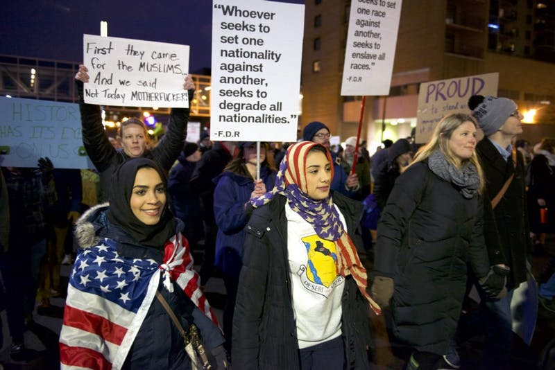 "Iraqi refugees Hawra Albattat and Saja Alnabi march through downtown Minneapolis to protest President Donald Trump's immigration ban on Tuesday, Jan. 31, 2017. ""We can't go home and see our family now,"" Albattat said."