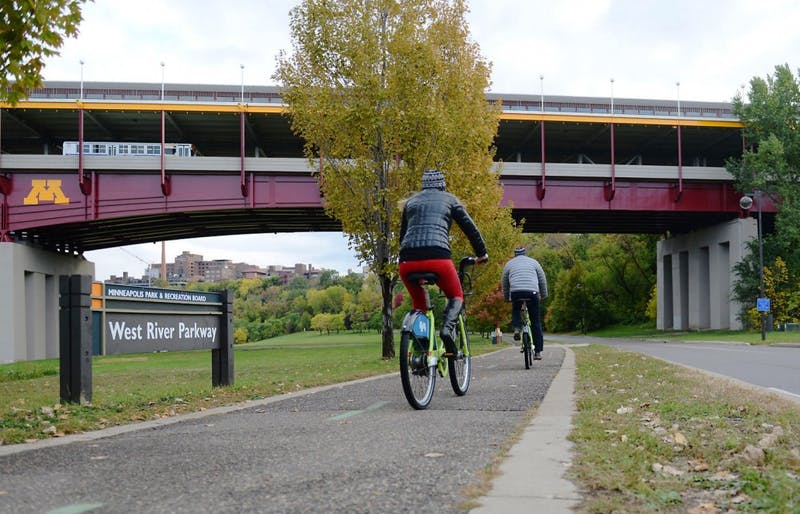 Pedestrians bike on the West River Parkway trail under Washington Avenue bridge on Saturday, Oct. 19, 2013. University students and faculty members disagree over whether to add concrete barriers to the sides to better prevent people jumping from the bridge.