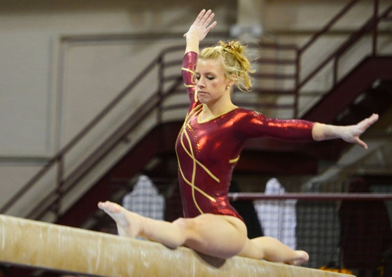 Senior Dusti Russell lands onto the beam in splits at the Sports Pavilion on Saturday afternoon.