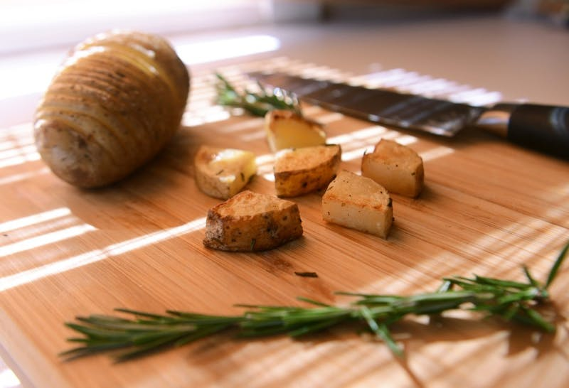 Hasselback or roasted potatoes, made with rosemary, olive oil, salt, and pepper.
