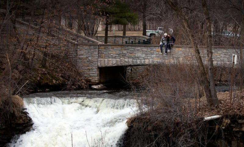 Brode Benish, a first year student at the University of St. Thomas and Sophia Rossman, a first year student at St. Catherine University, sit on Bridge 1 over Minnehaha Falls in Minnehaha Regional Park in Minneapolis on Wednesday, March 25.