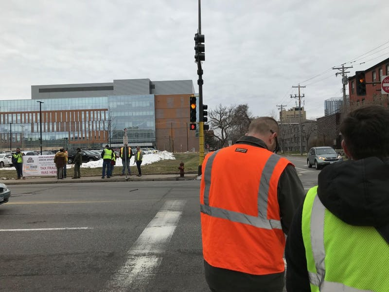 Advocates for construction workers' safety and treatment gathered to protest at the Arrow Apartments on Monday.