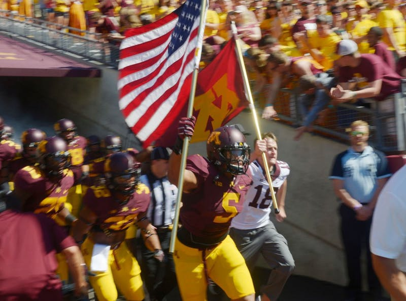 Damien Wilson runs onto the field on Sept. 6, 2014 at TCF Bank Stadium.