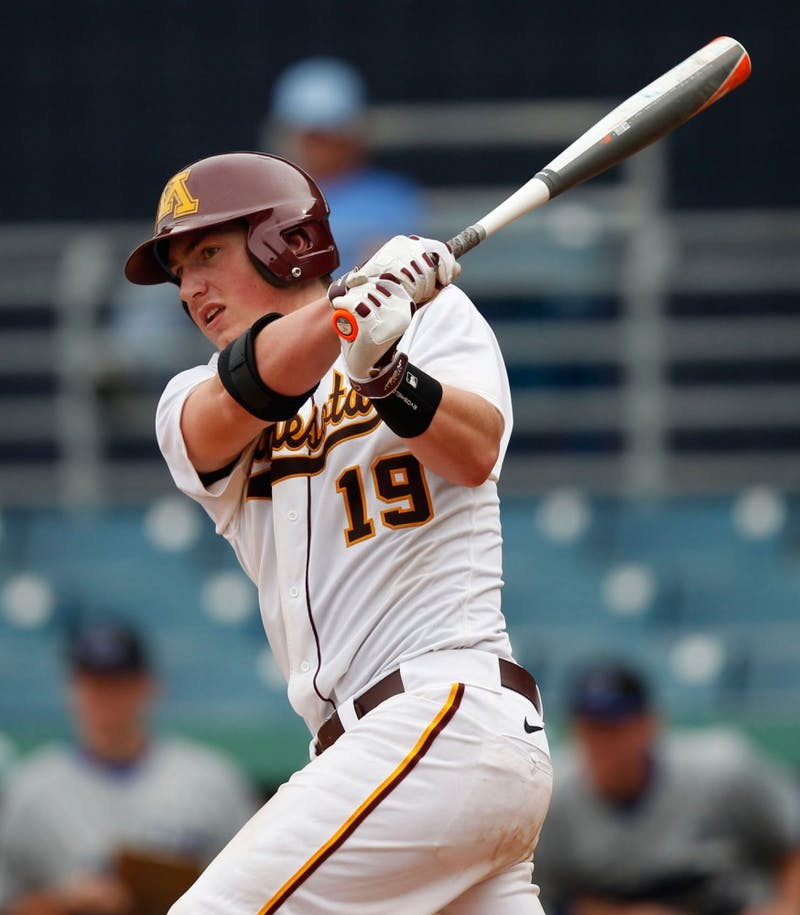 Gophers Austin Athmann swings at the ball on Friday, Feb. 21, 2014.