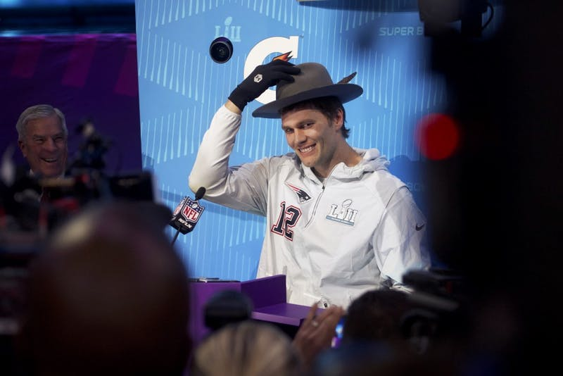 "New England Patriots quarterback Tom Brady tries on a hat passed to him by actor J.B. Smoove during the Super Bowl LII Opening Night event at the Xcel Energy Center on Monday. ""Brady looked better in it,"" Smoove said after their exchange."