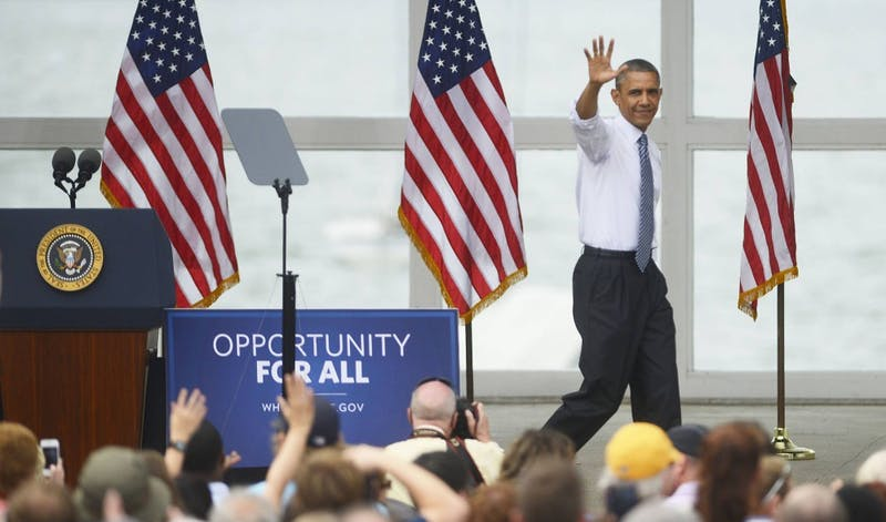 President Barack Obama waves goodbye to the crowd after giving a 30-minute speech on June 27, 2014, at the Lake Harriet Band Shell. He praised Minnesota legislation while criticizing Republicans in Congress for blocking his agenda.