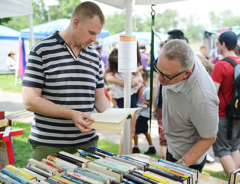 University professor Benjamin Munson and his partner Kevin Burk look through used books at the Twin Cities Pride festival Saturday.  Munson and Burk received domestic partnership benefits before they got married last summer.