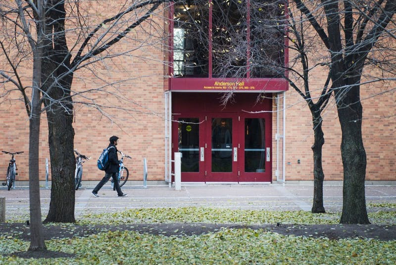A student walks past Anderson Hall on West Bank.