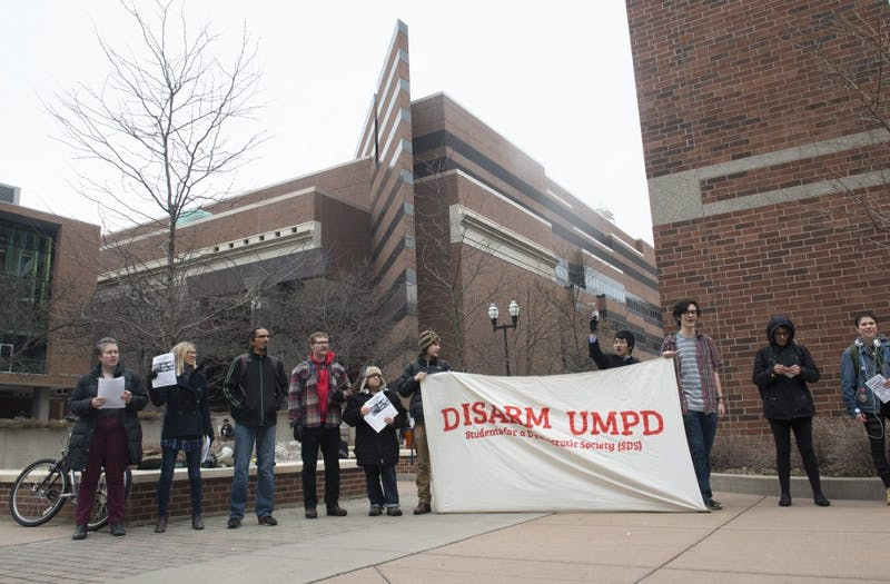 Members of Students for a Democratic Society stand outside of UMPD headquarters voicing concerns about the quantity of weapons at the department's disposal on Thursday, April 12.