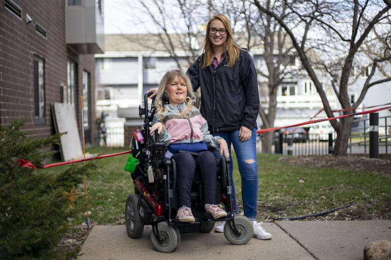 "Jen Onsum, left, and Paige Wolf, her personal care assistant pose for a portrait outside her apartment building on Wednesday, April 15. ""I have no choice but to trust that my PCAs are practicing social distancing and self-isolation,"" said Onsum."