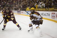 Freshman forward Sammy Walker eyes the puck during the game against the University of Minnesota Duluth on Sunday, Oct. 7 at Mariucci Arena.