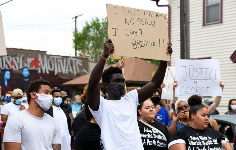 Protesters hold signs as they begin to march from Cup Foods on Chicago Ave S in Minneapolis to the Minneapolis 3rd Police Precinct on Minnehaha Ave on Tuesday, May 26. The protest was in response to the death of George Floyd in police custody. (Andy Kosier / Minnesota Daily)