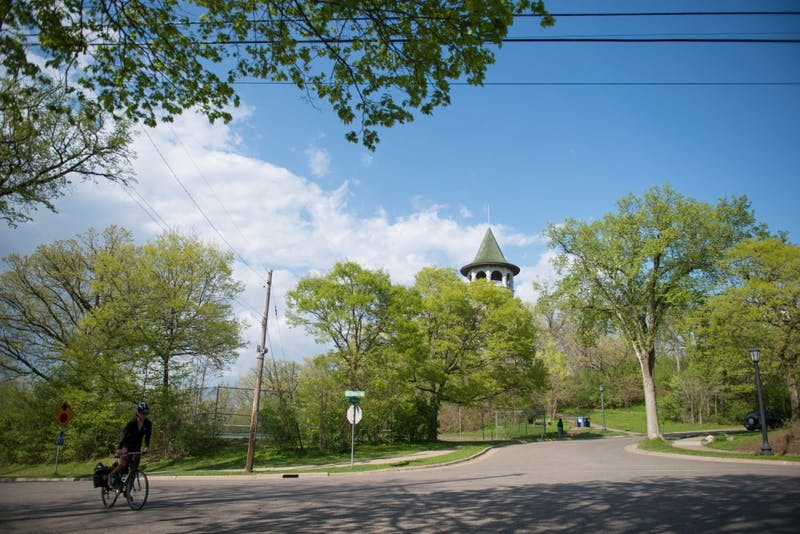 A woman bikes past the witch's tower on southeast Orlin avenue  Tuesday Afternoon. Although about half of the neighborhood is made up of students, currently no student is part of the Prospect Park Association.