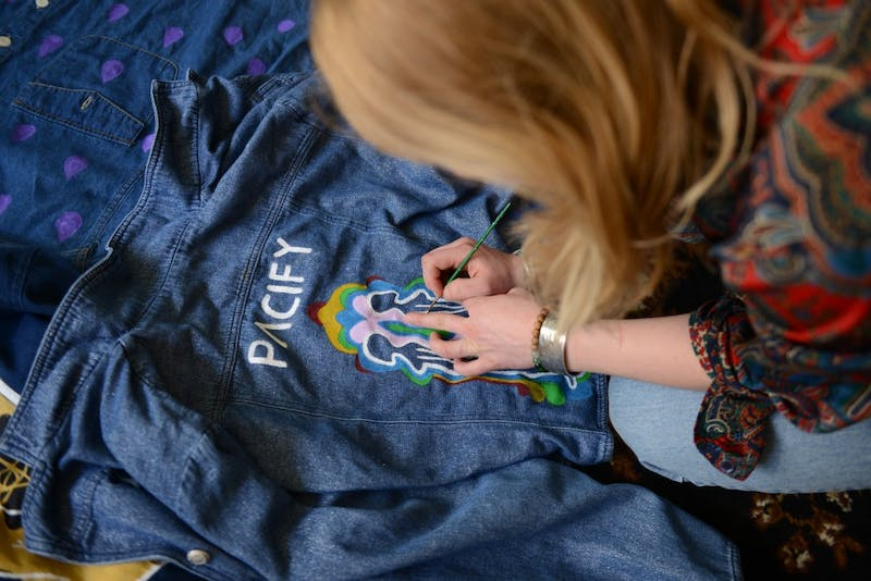Maddie Bolatto paints a jacket for local clothing brand, Pacify. The brand, created by three local female artists, focuses on creating original pieces from thrifted clothing.