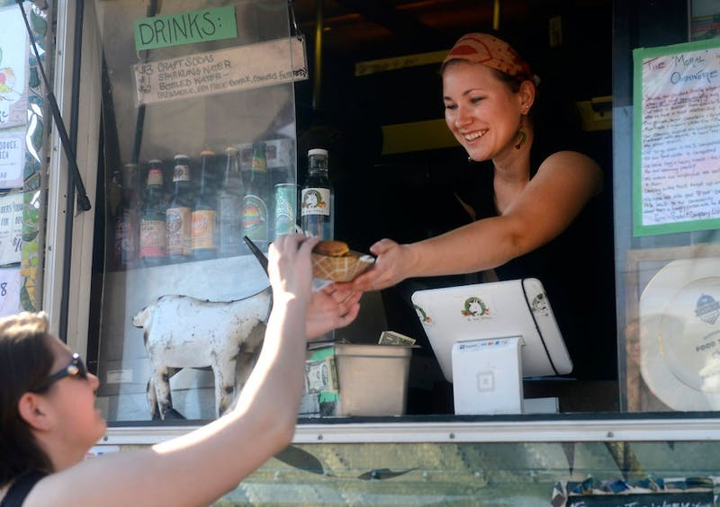 Vendor of The Moral Omnivore food truck, Lannea Logas, serves a customer at the Midtown Farmer's Market on Saturday morning. The market allows people to explore more healthy food options.