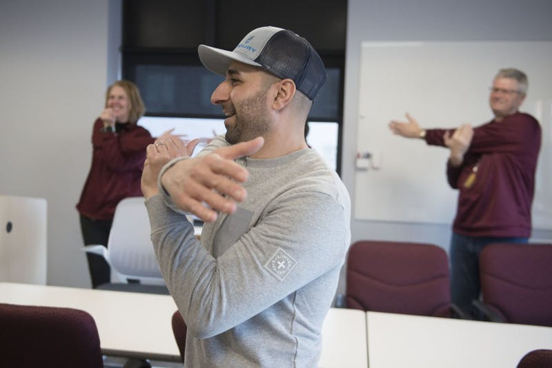 Nael Banat leads University Human Resources employees in a pre-shift stretch on Friday, Feb. 15. The program was started by Banat and fellow graduate student Andrea Santi as part of their Kinesiology studies.