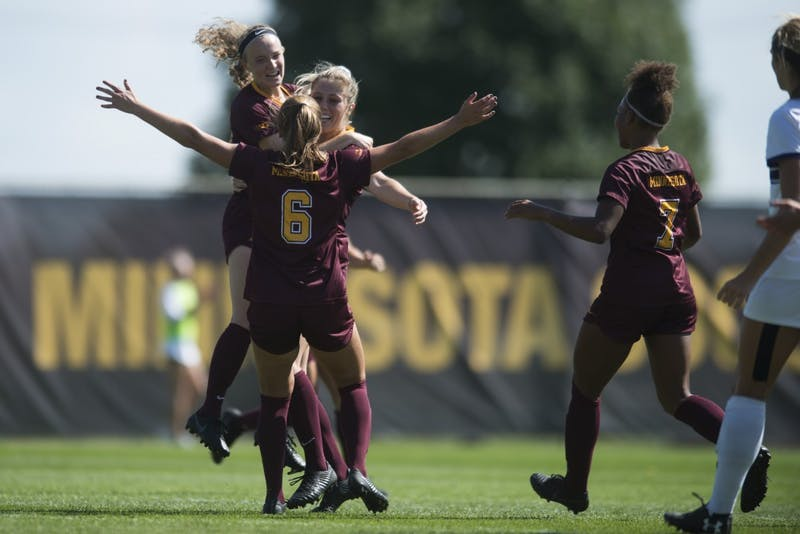 Gophers April Bockin, Emily Peterson and Molly Fiedler celebrate a penalty kick scored by Bockin at Elizabeth Lyle Robbie Stadium on Sunday, Sept. 16.