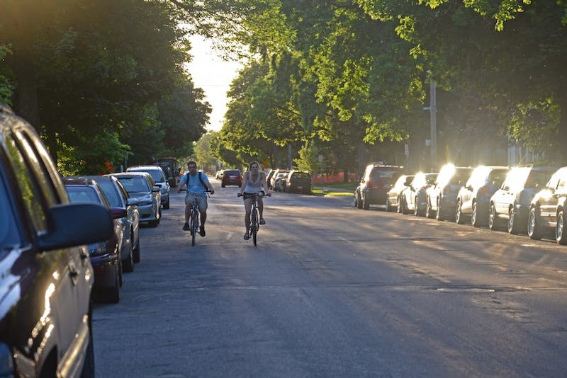 Bikers ride beside crowded parking on both sides of Eighth Street Southeast in Minneapolis on June 6, 2017.
