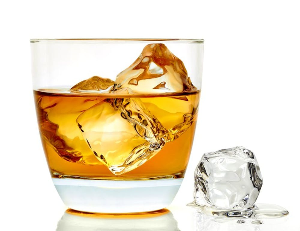 Whiskey with ice cubes in rocks glass on white background