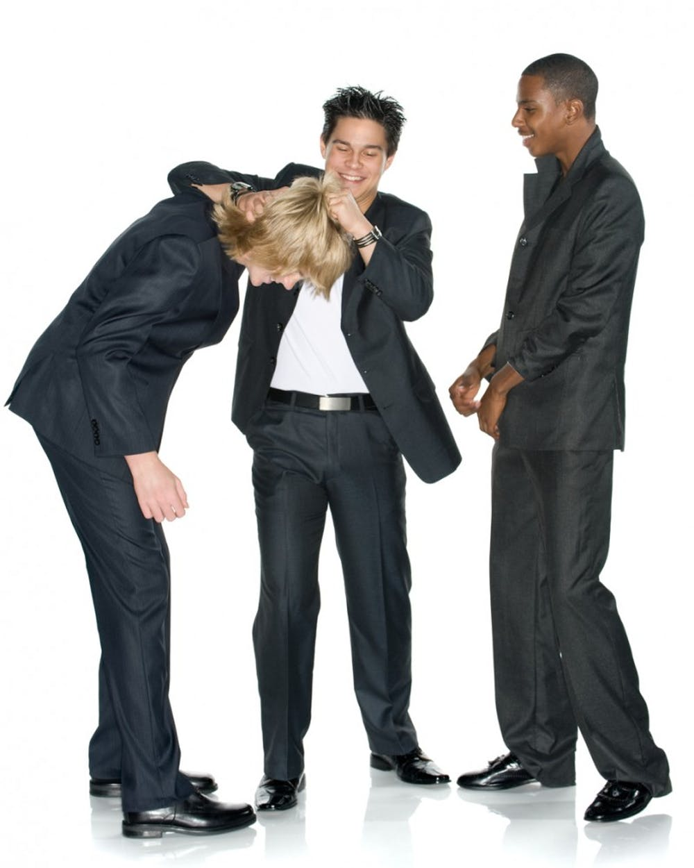 """Fun, light, and lively image of three young business men. Asian American man is giving a noogie to the new guy. Studio shot. Isolated on white."""