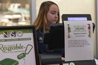 Mallory Walsh waits to swipe students into Nelson Court during the meal swipe donation pilot program on Oct. 5. (FILE)