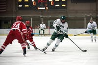 Ohio University defenseman Thomas Pokorney (No. 4) dekes the puck against Stony Brook forward Matthew McDermitt (No. 74). Ohio went on to win against Stony Brook 3-1. (FILE)