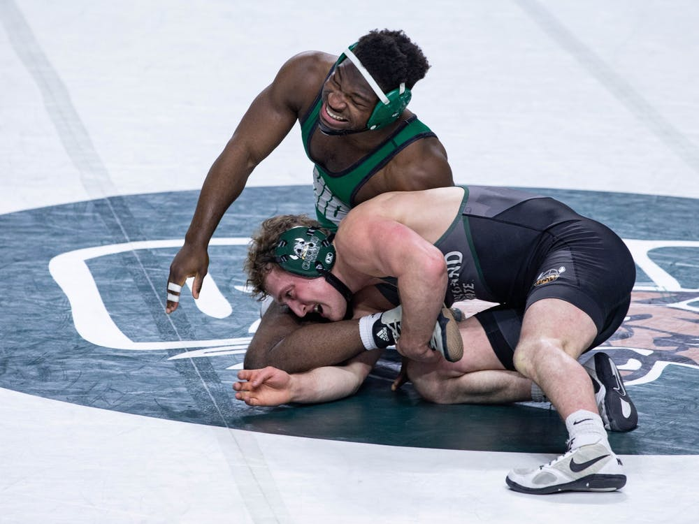 Ohio's Kamal Adewumi is grabbed by Cleveland State's Riley Smucker in a match held in the Convocation Center on Sunday, Feb. 14, 2021.