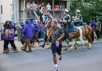 Members of Omega Psi Phi march down Stewart Street as mounted police push them back onto the sidewalk on Saturday.