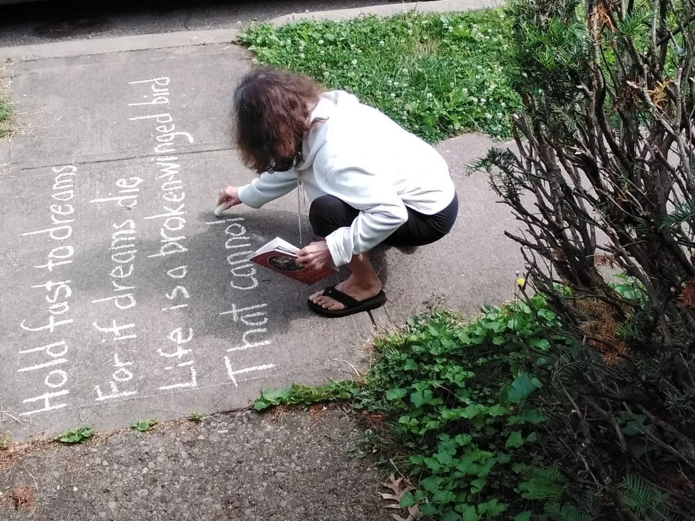 Athens, Ohio, Poet Laureate Wendy McVicker chalks poems on the sidewalk by her house. Photo provided by McVicker.