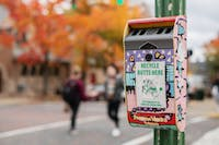 A cigarette butt recycling box sits on a light pole at the intersection of Court Street and East Washington Street in Athens, Ohio.