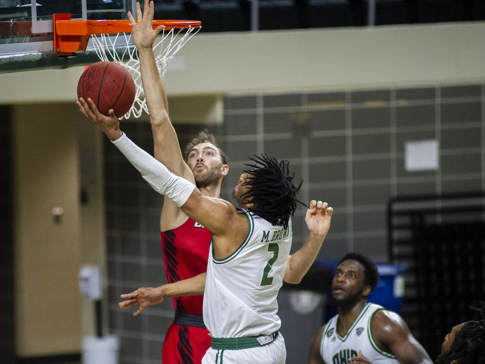 Ohio University guard, Miles Brown (2), takes the ball to the basket with heavy defense from Ball State during the home game on Saturday, Jan. 23, 2021, in Athens Ohio.