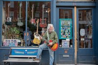 Frank McDermott poses for a portrait outside his music store, Blue Eagle Music in Athens, Ohio.