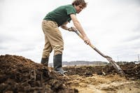 Alex Armstrong, a junior at Ohio Univeristy, spreads out dirt in order to make a bed at the West State Street Research Site in Athens, Ohio, on Friday, March 29, 2019. As a part of his Sustainable Agriculture class, Armstrong is required to work 10 hours at the site.