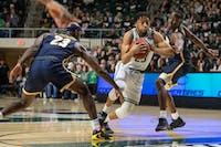 Ohio's Miles Brown (#23) attempts to move past Toledo's Willie Jackson (#23) and Keshaun Saunders (#24) during their game in The Convocation Center on Tuesday, Jan. 21, 2020. Ohio lost the game 83-74.