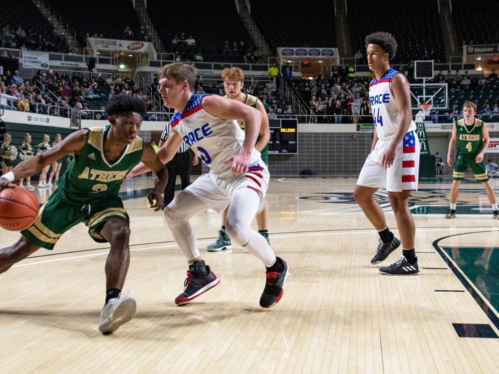 Athens' Elijah Williams attempts to drive past Zane Trace's Colby Swain during their District Semifinals tournament game on Thursday, Feb. 28. The Bulldogs lost to the Pioneers 48-28. (FILE)