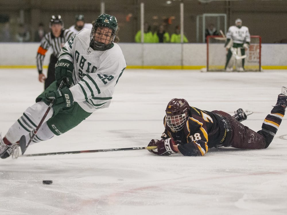 Ohio forward Tyler Harkins (22) gets tripped up while skating in the offensive zone during the Bobcats hockey game on Saturday, January 11, 2020, at Bird Arena in Athens, Ohio.
