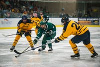 Junior forward Gianni Evangelisti (#7) fights for the puck in the third period of Ohio's game against West Virginia in Bird Arena Friday. The Bobcats defeated the Mountaineers 12-1.