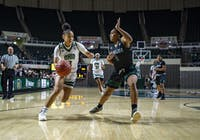 Ohio University's Amani Burke (#3) drives towards the basket against Eastern Michigan's Courtnie Lewis (#4).