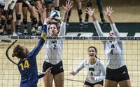 Katie Nelson (#2) and Sara Januszewki (#4) blocking a hit from Kent State while setter Vera Giacomazzi (#6) waits for a deflection off the block during Thursday's game.